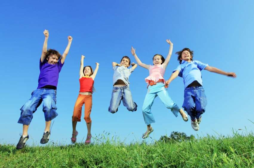 Group of five happy children jumping on meadow by LIGHTTRUE
